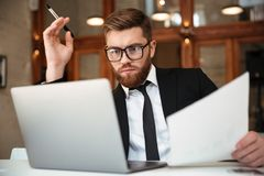 Young concentrated bearded businessman in formalwear looking at. Laptop screen holding papers while sitting at workplace Stock Photos