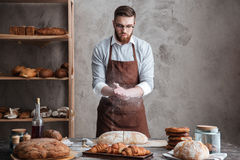 Young concentrated bearded man wearing glasses baker royalty free stock image