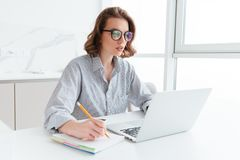 Young concentrated brunette woman in glasses wokking with laptop royalty free stock photos