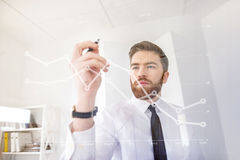 Young concentrated business man drawing chart on the virtual screen. In office stock photo