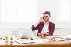 Young concentrated businessman has a mobile talk in modern white office Stock Images