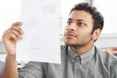 Young concentrated businessman holding paper indoors Royalty Free Stock Photography