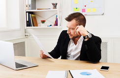 Young concentrated businessman read documents in modern white office Royalty Free Stock Photos