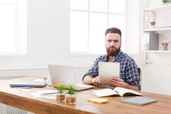 Young concentrated man using tablet at the table with laptop. Young concentrated businessman using tablet in modern white office Royalty Free Stock Images