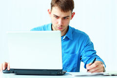 Young concentrated businessman writing notes down and looking at laptop Royalty Free Stock Photos