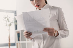 Young concentrated businesswoman reading documents in office Royalty Free Stock Photography