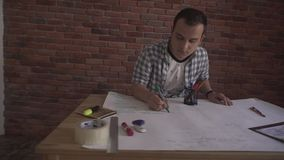 Young concentrated confident attractive man in plaid shirt working on business project thinking sitting by wooden table stock footage
