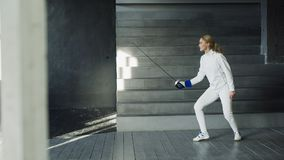 Young concentrated fencer woman practice fencing exercises and training for Olympic games competition in studio indoors. Concentrated fencer woman practice Stock Photo