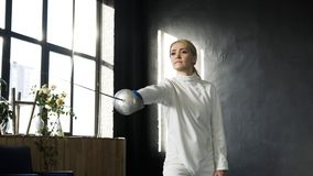 Young concentrated fencer woman practice fencing exercises and training for Olympic games competition in studio indoors. Concentrated fencer woman practice Royalty Free Stock Photography