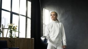 Young concentrated fencer woman training fencing exercise in studio indoors. Concentrated fencer woman training fencing exercise in studio indoors Royalty Free Stock Photos