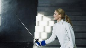 Young concentrated fencer woman training fencing exercise in studio indoors. Concentrated fencer woman training fencing exercise in studio indoors Stock Images