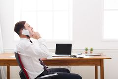 Young concentrated male administrator in shirt has a mobile talk in modern white office. Royalty Free Stock Photography