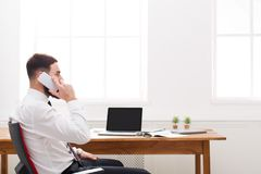 Young concentrated male IT manager in shirt has a mobile talk in modern white office. Royalty Free Stock Photos