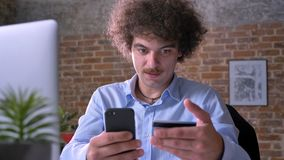 Young concentrated man with curly hair and mustache using credit card and holding phone sitting at table in modern stock video