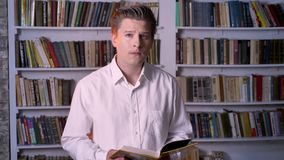 Young concentrated man is reading book in library, watching at camera.  stock footage
