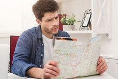 Young man reading map, planning vacation. Young concentrated man reading map at home. Handsome guy preparing for vacation, planning route of trip, copy space Stock Images