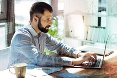 Young concentrated man sitting and working with laptop. Technologies in life. Young confident concentrated man sitting in the office by the table working with Royalty Free Stock Images
