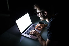 Young concentrated man using laptop computer at home indoors at night looking at laptop white screen Royalty Free Stock Images