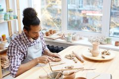 Potter working with clay. Young concentrated mixed-race male ceramist preparing clay while modeling pots in workshop Stock Images