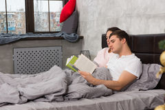 Young concentrated pair reading books while lying in the bed, ou Royalty Free Stock Photo