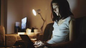 Young concentrated woman using laptop computer and typing message at home in night time. Young concentrated serious woman working at night time using laptop stock video