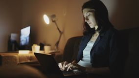 Young concentrated woman working at night using laptop computer and typing message. Young concentrated serious woman working at night time using laptop computer stock video footage