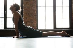 Young concentrated sportsman stretching muscles on the fitness mat Stock Image