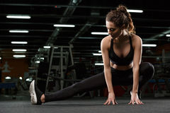 Young concentrated strong fitness lady make stretching exercise Royalty Free Stock Photo