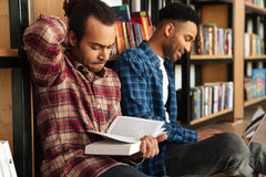 Young concentrated two african men reading books using laptop. Picture of young concentrated two african men students sitting in library reading books using royalty free stock photos