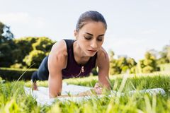 young concentrated woman doing plank on grass meadow royalty free stock image