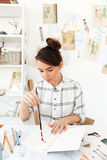 Young concentrated woman fashion illustrator. Photo of young concentrated woman fashion illustrator sitting at the table and drawing. Looking aside Royalty Free Stock Photos