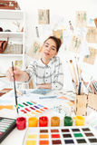 Young concentrated woman fashion illustrator. Picture of young concentrated woman fashion illustrator sitting at the table and drawing. Looking aside Royalty Free Stock Photography