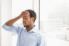 Young concentrating businessman leaning with his back against a window Royalty Free Stock Photo