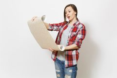 Young concerned beautiful woman in casual clothes holding unrolled wallpaper roll isolated on white background. Instruments, accessories, tools for renovation royalty free stock photography