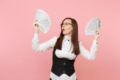 Young concerned business woman in glasses holding bundle lots of dollars, cash money spreading hands isolated on pink. Background. Lady boss. Achievement career stock image