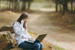 Young concerned business woman or student in casual clothes sitting on stone talking on mobile phone in city park or stock photography