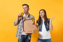 Young concerned couple woman man sport fans cheer up support team drinking beer hold italian pizza in cardboard flatbox stock image