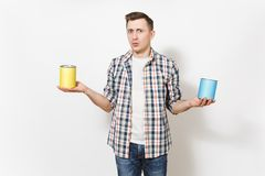 Young concerned man in casual clothes holding empty paint tin cans with copy space isolated on white background. Instruments, accessories, tools for renovation stock image