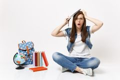 Young concerned puzzled woman student in glasses hold pencil, notebook clinging to head sit near globe backpack, school royalty free stock photography