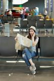Young concerned traveler tourist woman holding paper map search route clinging to face wait in lobby hall at airport. Passenger traveling abroad on weekend stock image