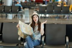Young concerned traveler tourist woman holding paper map search route spreading hands wait in lobby hall at airport. Passenger traveling abroad on weekends royalty free stock image