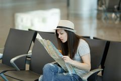 Young concerned traveler tourist woman holding paper map, search route, wait in lobby hall at international airport. Passenger traveling abroad on weekends stock photos