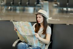 Young concerned traveler tourist woman holding paper map, search route, wait in lobby hall at international airport. Passenger traveling abroad on weekends royalty free stock photo