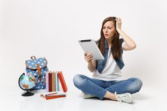 Young concerned woman student holding using tablet pc computer keeping hand on head sitting near globe, backpack school. Books isolated on white background stock image