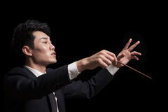 Young conductor with baton raised, black background Stock Image