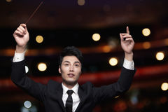 Young conductor with baton raised at a performance Royalty Free Stock Photo