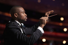 Young conductor with baton raised at a performance Royalty Free Stock Photos