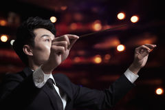 Young conductor with baton raised at a performance Royalty Free Stock Images