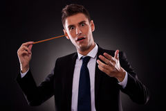 Young conductor sticking his baton in his ear Stock Photography