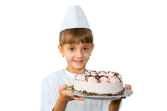 The young confectioner. The little girl the confectioner is photographed with a cake Stock Photography